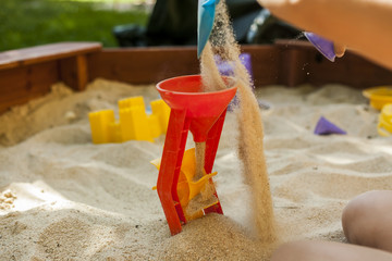 Hands throwing sand in a plastic mill toy in a sandbox. Movement