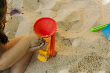 Hands throwing sand in a plastic mill toy in a sandbox. Movement. High angle