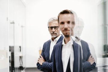 Portrait of two businessmen at glass pane