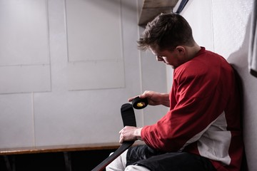 Male player taping ice hockey stick