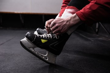 Low section of hockey player tying ice skate