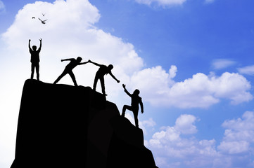 silhouette people helping hand to climb mountain rock, concept as winner, improvement and goal to success in business and sport
