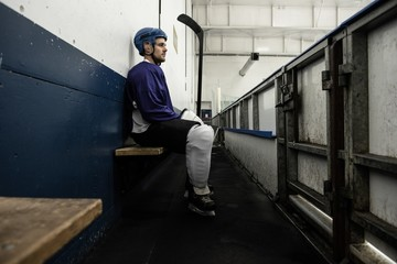 Ice hockey player on seat at corridor