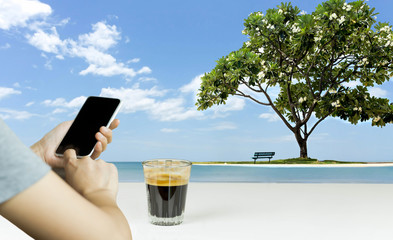 Hand using cell phone and coffee with beautiful frangipani tree with chair on the beach