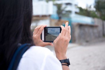 Woman traveler taking picture of the beach with cell phone