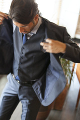 Businessman in suit putting on jacket