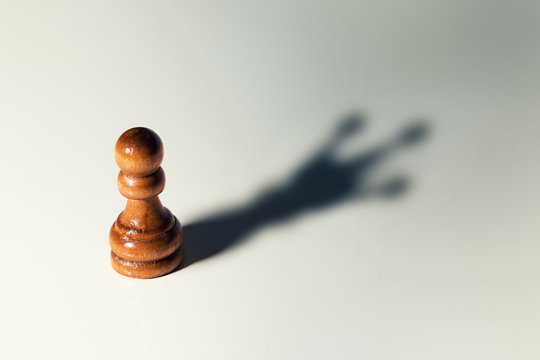 trust yourself concept - chess pawn with king shadow
