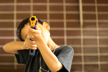 Little boy playing with a toy gun against