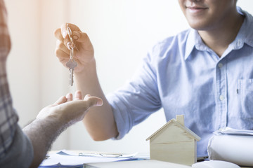 Businesman or customer gets key of house from broker after finishing contract