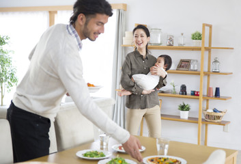 Man preparing meals at dining and woman smiling with baby