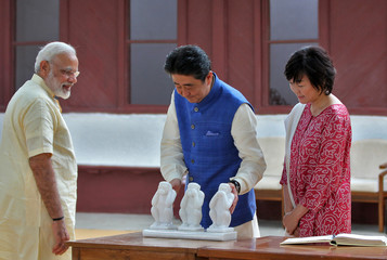 Japanese PM Abe touches a sculpture of three monkeys as his wife, Akie Abe, and India's PM Modi look on during their visit to Gandhi Ashram in Ahmedabad