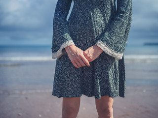 Woman with folded hands on beach