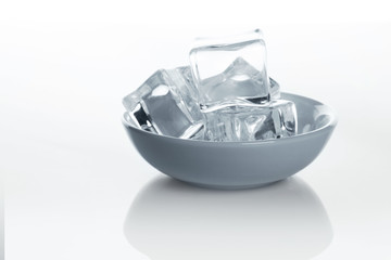 Bowl with ice cubes on white background