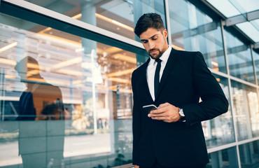 Businessman using mobile phone at airport