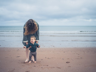 Mother helping baby walk on the beach