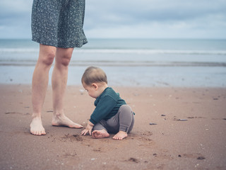 Little baby playing by legs of mother on beach
