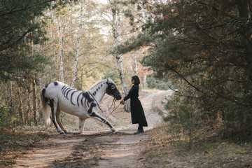 Beautiful woman in black standing behind her white horse (painted as skeleton) in the autumn forest. Horse is taking a bow