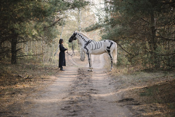 Beautiful woman in black standing behind her white horse (painted as skeleton) in the autumn forest.