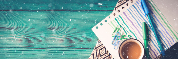 Cup of coffee, notebook and pens on dark green wooden background. Winter mood backdrop long banner
