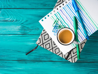 Cup of coffee, notebook and pens on dark green wooden background. Winter mood backdrop