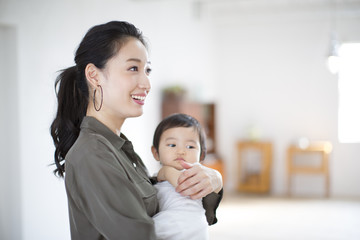 Woman holding baby and smiling