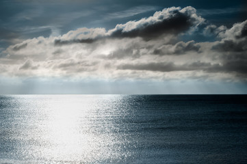 Shimmering Light on Sea with Moody Dark Sky