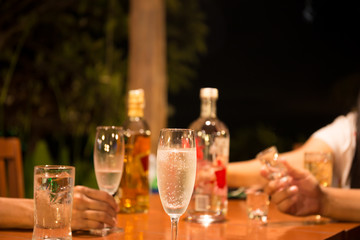 Group of friends enjoying drinking a glass of champagne and whisky at party