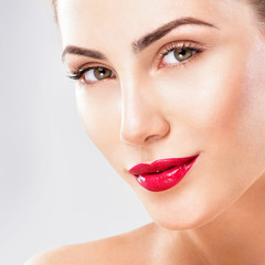 Beautiful face of young adult woman with clean fresh skin. Red lipstick