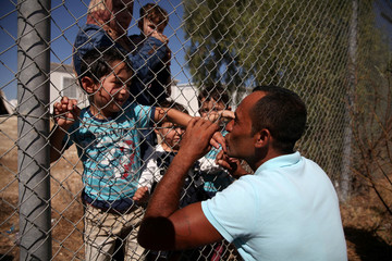 A Picture and its Story: Syrian family shares kisses through fence