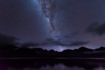 Milky Way landscape. Clearly Milky way above Lake Segara Anak inside crater of Rinjani mountain on night sky. Lombok island, Indonesia.