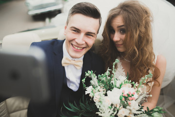 Happy bride and groom making selfie at their wedding in retro car