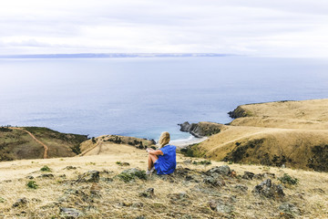 Rear view of woman sitting at Blowhole Beach