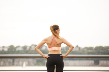 Rear view of woman with hands on hip looking away while standing on bridge
