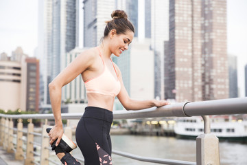 Smiling woman stretching leg while standing on bridge in city