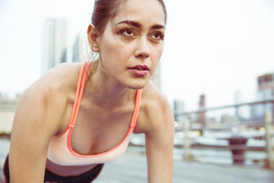 Woman looking away while exercising on bridge