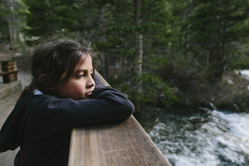 Thoughtful girl looking away while leaning on bannister at Inyo National Forest