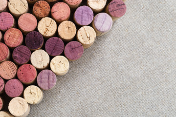 Wooden cork close-up of bottles with red and white wine located diagonally.
