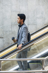 Side view of businessman standing on escalator