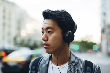 Businessman looking away while listening music in city