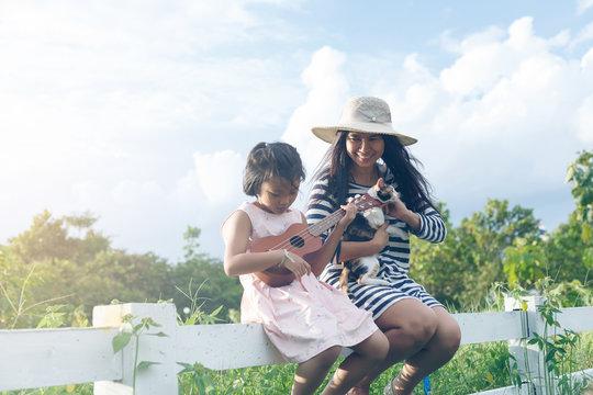 The girl is playing  Ukulele