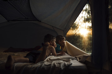 Thoughtful brothers looking through window while lying in tent