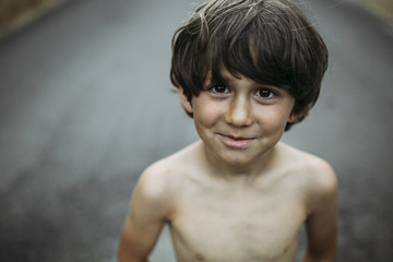 High angle portrait of shirtless boy on country road