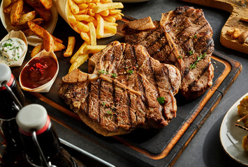 Roasted steak served with french fries and dips