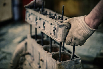 Cropped hand of mechanic holding machinery in workshop