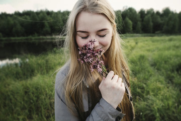 Woman smelling flowers while standing by lake