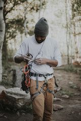 Man attaching carabiners on rope