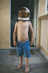 Portrait of boy in space helmet standing in porch