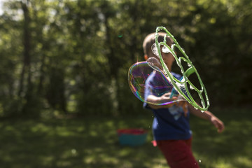 Boy blowing bubble using bubble wand in yard