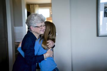 Grandmother embracing granddaughter at home