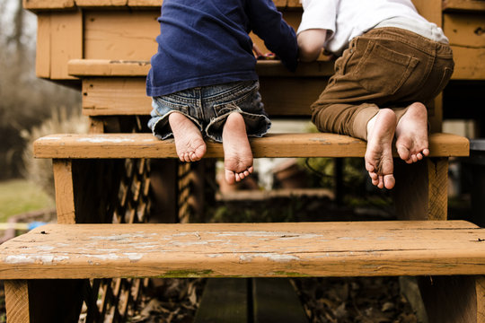 Low section of brothers playing while kneeling on steps at playground